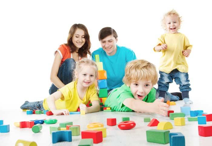 Eltern und Kinder spielen mit Holz Lernspielzeug depositphotos.com
